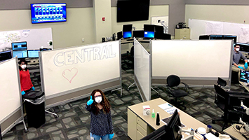 A person wearing a mask and gloves gives a thumbs up in a PPL control room